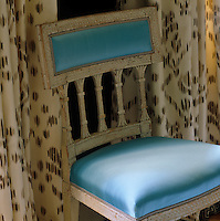 A chair upholstered in blue satin stands in front of custom-coloured Ikat curtains printed on dressmaker's satin