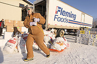 "February 16, 2013  Volunteer Andi Malard helps unload  musher food bags bound for the Rainy Pass checkpoint from a van and stack them to be loaded into volunteer Iditarod Air Force planes at the Willow Airport during day one of the ""Food Fly""...Photo Copyright Jeff Schultz  -- Do not reproduce without written permission"