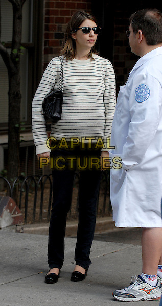 SOFIA COPPOLA.Director Sophia Coppola walks near the site where investigators remove the wreckage of a small plane that struck a residential high-rise building in New York after attending a Doctors appointment at the Hospital for Special Surgery. The accident killed New York Yankees player Cory Lidle, New York, NY, USA..Ref: ADM/PH.full length Sophia Copolla Coppolla black white striped stripes top sunglasses shades purse bag trousers.www.capitalpictures.com.sales@capitalpictures.com.©AdMedia/Capital Pictures.