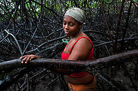 A Colombian girl rests during searching for shellfish in the mangrove swamps on the Pacific coast, Colombia, 12 June 2010. Deep in the impenetrable labyrinth of mangrove swamps on the Pacific seashore, hundreds of people struggle everyday, searching and gathering a tiny shellfish called 'piangua'. Wading through sticky mud among the mangrove tree roots, facing the clouds of mosquitos, they pick up mussels hidden deep in mud, no matter of unbearable tropical heat or strong rain. Although the shellfish pickers, mostly Afro-Colombians displaced by the Colombian armed conflict, take a high risk (malaria, poisonous bites,...), their salary is very low and keeps them living in extreme poverty.