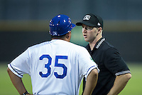 Umpire Mark Stewart listens as Burlington Royals hitting coach Jesus Azuaje (35) argues a call at first base during the game against the Bluefield Blue Jays at Burlington Athletic Stadium on June 27, 2016 in Burlington, North Carolina.  The Royals defeated the Blue Jays 9-4.  (Brian Westerholt/Four Seam Images)