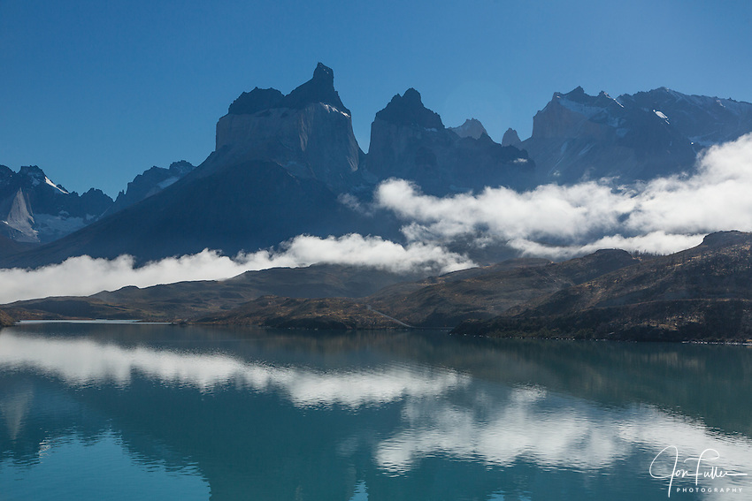 Clearing fog over Lago Pehoe. A few low clouds remain, obscuring the bases of the Cuernos del Paine.  To the right of the Cuernos, the tops of Torre Sur and Torre Central are visible.  At far right is Monte Almirante Nieto.  The still waters of the lake provide a mirror-like reflection of the peaks. Torres del Paine National Park, Patagonia, Chile.  A UNESCO World Biosphere Reserve.