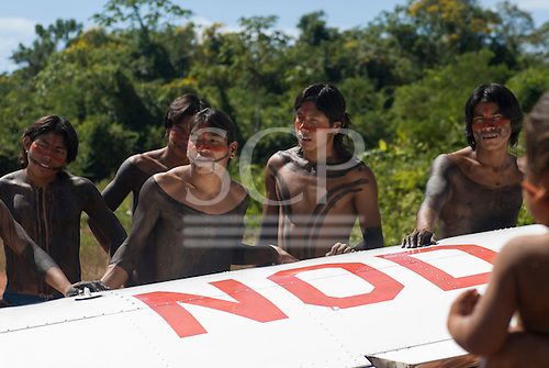 Pará State, Brazil. Aldeia A-Ukre (Kayapó). Warrior leaders from the village in traditional body paint greet an arriving plane.