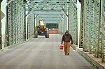 A worker crosses the Duboistown bridge before charges were set off dropping the south half of the bridge to the causeway beneath the bridge.