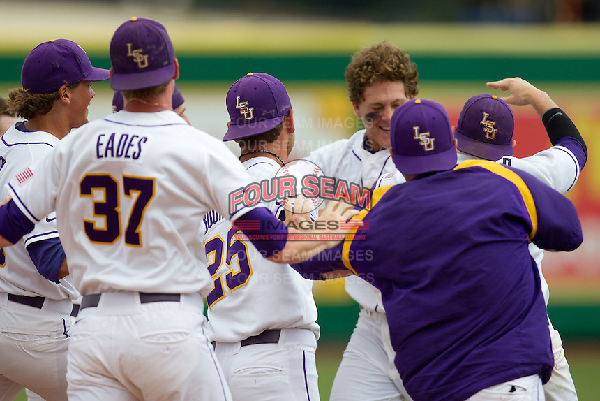 LSU Tigers outfielder Mason Katz #8 is mobbed by his teammates following his game winning RBI to decide the continuation of their suspended NCAA Super Regional baseball game against Stony Brook on June 9, 2012 at Alex Box Stadium in Baton Rouge, Louisiana. LSU defeated Stony Brook 5-4 in 12 innings. (Andrew Woolley/Four Seam Images)
