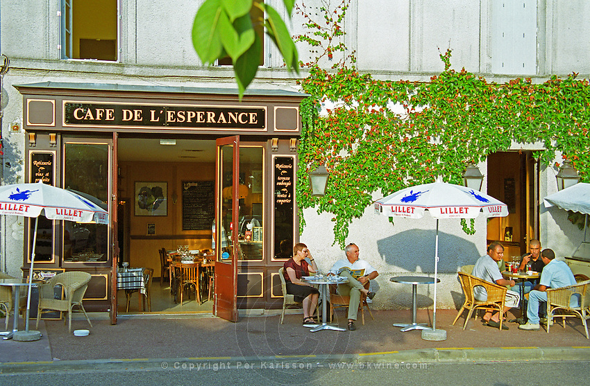 Cafe de l'Esperance in Bouliac in afternoon sunlight. Typical French traditional cafe with people sitting outside on the terrace drinking wine, beer, coffee. Sun shading umbrellas parasol with text Lillet. A couple at one table and three men in wicker chairs at another table. Bordeaux Gironde Aquitaine France Europe