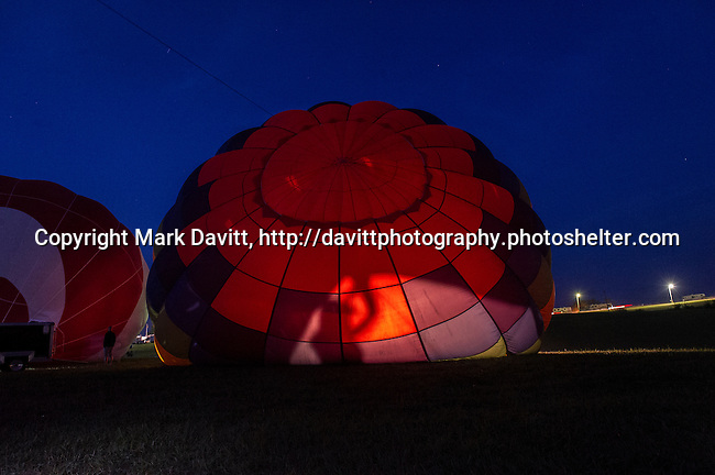 A balloon crew member's shadow is cast inside a balloon in the very early hour before dawn at the National Balloon Classic, Indianola, Iowa.