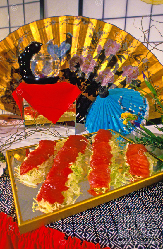 An Asian-inspired table setting with a mouth-watering tray of local shashimi on an oriental tablecloth with a background of a flared golden fan and shoji screens