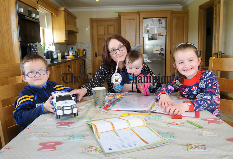 Mairead Mahoney with her three children; five year old Darragh, seven year old Emma and fifteen month old Oisín at home in Moveen. photograph by John Kelly.