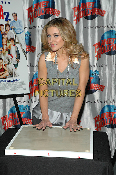 """CARMEN ELECTRA.Promotes her new film, """"Cheaper By The Dozen 2"""" at Planet Hollywood in Times Square in New York City. .December 19th, 2005.Photo: Patti Ouderkirk/AdMedia/Capital Pictures.Ref: PO/ADM.half length grey gray vest pearl necklace mould hands gesture.www.capitalpictures.com.sales@capitalpictures.com.© Capital Pictures."""