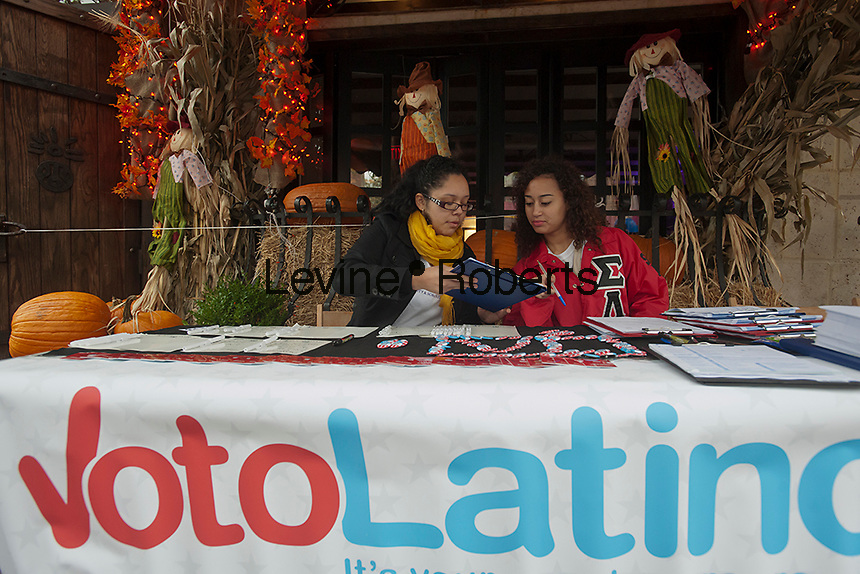 Yeimmy Torrez, left, and Dabrali Diaz, right, at the voter registration table at Mamajuana restaurant.The volunteers are members of the Sigma Lambda Upsilon sorority.  VotoLatino organizes a voter registration block fair on Dyckman Street in the Inwood neighborhood of New York on Sunday, October 7, 2012, 2012. The voting block of Hispanics has become increasingly important in both local and national elections.(© Richard B. Levine)