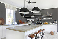 A contemporary kitchen with concrete flooring and work surfaces and pendant lights from Catellani & Smith