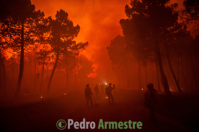 A firefighter walks past trees on fire during a wildfire in Tabuyo del Monte near Leon, Spain, on Tuesday August 21, 2012. Some 500 soldiers have been deployed to help battle a wildfire authorities believe was started intentionally and which has burned 80 sq. kilometers (30. sq. miles) in northern Spain. (c)Pedro Armestre