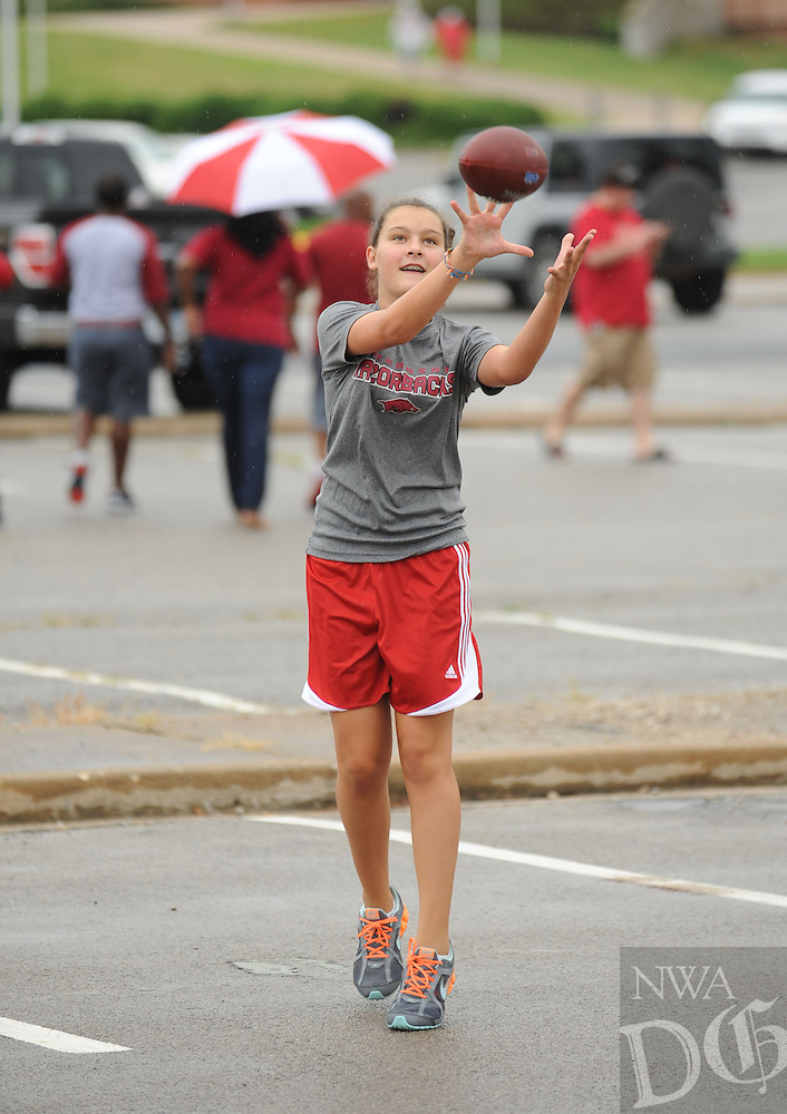 STAFF PHOTO ANDY SHUPE - Cheyenne Hillman, 12, of Springdale reaches to catch a football while tailgating prior to the start of the University of Arkansas' football game with Nicholls State Saturday, Sept. 6, 2014, at Razorback Stadium in Fayetteville.
