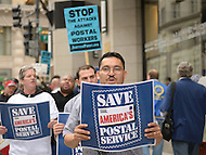 November 21, 2011  (Washington, DC)  Jorge Lopez (center), of the Sheet Metal Workers Local 100, holds a sign as he protests in front of the National Press Building in Washington to rally against cuts within the Postal Service.  U.S. Postmaster General Patrick R. Donahoe was inside speaking to members of the National Press Club.   (Photo by Don Baxter/Media Images International)
