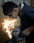 Sparks fly as a youth in the metalworking class at the Vocational Training Center in Gaza City, Gaza, uses a grinder. The center is run by the Department of Service for Palestinian Refugees of the Near East Council of Churches, a member of the ACT Alliance, and funded in part by the Pontifical Mission for Palestine.