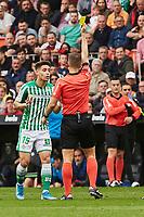 29th February 2020; Mestalla, Valencia, Spain; La Liga Football,Valencia versus Real Betis; Referee Cordero Vega shows a yellow card to Alex Moreno of Real Betis