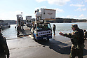 OSHIMA, Japan - A Japanese utility repair vehicle drives off a U.S. Navy landing craft docked here, March 27. The 31st Marine Expeditionary Unit and Amphibious Squadron 11 picked up Japanese utility repair vehicles from the port in Kessenuma and delivered food, water, comfort items and the vehicles to residents on this isolated island. The island of Oshima has been cut off from the mainland since the earthquake and tsunami March 11. The operation demonstrated the expeditionary capabilities in ship-to-shore amphibious operations. Marines and Sailors of the 31st MEU are conducting humanitarian aid and disaster relief missions in northeast Japan assisting the Japanese Self Defense Forces in their ongoing operations. (Photo by USMC/AFLO) [0006]