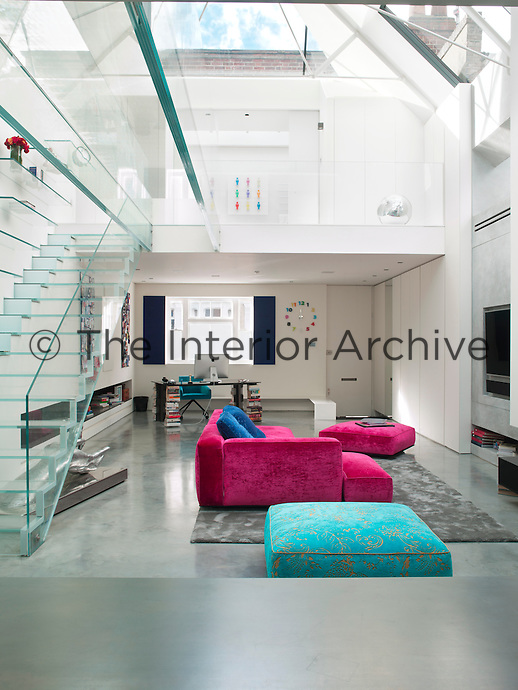 The open plan living room, extended into a double height atrium, including two mezzanines, is bathed in light from the skylight above