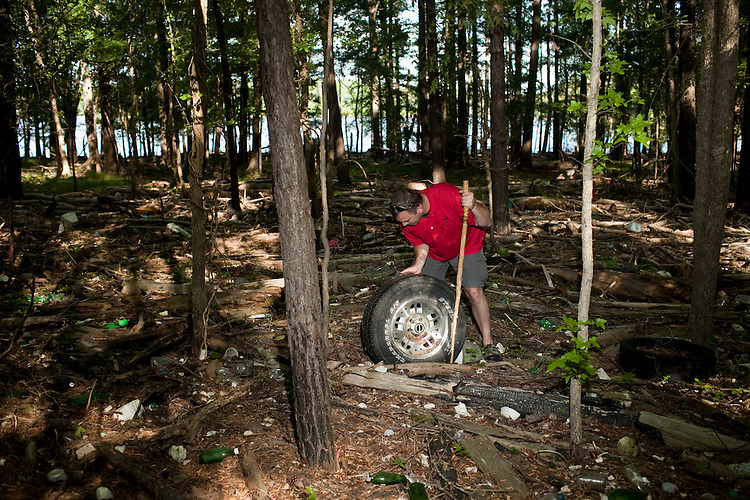 Colson finds a tire among the debris at the high water mark of Jordan Lake comprised of anything that has floated down the Haw River since Jordan Lake was damned.