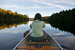 A woman paddles a canoe through the glass-like Galerairy lake in Ontario's Algonquin Provincial Park in Canada.