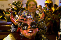 A woman shows her mask at the Carnaval de Oruro. During the fiesta many people sacrifice llamas and give offerings such as coca leaves and cigarettes to show their dedication to the Devil, a Virgin, Pachamama or Mother Earth. The Devil (or Uncle) is a mythical character that protects the miners of Oruro who work in dangerous conditions hundreds of metres below the ground. During the carnival, people dress in outrageous costumes and dance for days before arriving at the Church of Socavon, where they pay their respects to a virgin. Ironically, many of the dancers wear devil costumes.