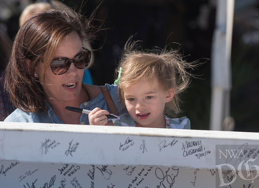 NWA Democrat-Gazette/J.T. WAMPLER Jenessa Bailey of Fayetteville helps her daughter Maye, 3, sign a steel beam Wednesday Sept. 28, 2016 at the Arkansas Children's Hospital Northwest's topping out ceremony. The beam represents the highest point on the skeleton of the structure as it gets closer to its early 2018 opening. The hospital is located at the Corner of 56th Street and Watkins Avenue in Springdale.