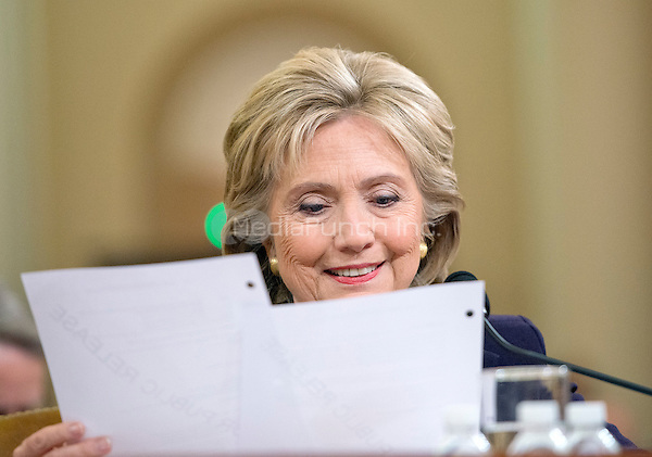 Former United States Secretary of State Hillary Rodham Clinton, a candidate for the 2016 Democratic Party nomination for President of the United States, smiles as she reads a memo from Ambassador J. Christopher Stevens, the US envoy to Libya who was killed in the terror attack in Bengazi on September 11, 2012 as she testfies before the US House Select Committee on Benghazi on Capitol Hill in Washington, DC on Thursday, October 22, 2015.<br /> Credit: Ron Sachs / CNP/MediaPunch<br /> (RESTRICTION: NO New York or New Jersey Newspapers or newspapers within a 75 mile radius of New York City)