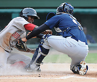 Outfielder Felix Sanchez (34) of the Greenville Drive is safe at home as catcher Gary Sanchez (35) of Charleston RiverDogs applies a late tag in a game on July 31, 2011, at Fluor Field at the West End in Greenville, South Carolina. The Drive wore throwback jerseys honoring the textile mill baseball teams. (Tom Priddy/Four Seam Images)