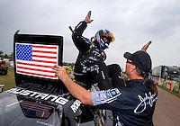 Apr 27, 2014; Baytown, TX, USA; NHRA funny car driver Robert Hight celebrates with a crew member after winning the Spring Nationals at Royal Purple Raceway. Mandatory Credit: Mark J. Rebilas-