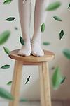 Photograph of a girl's legs above a wood stool with green leaves falling around