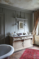 A modern basin on a washstand is set against a grey panelled wall in a bathroom with stripped floorboards and a distressed finish effect on the ceiling.