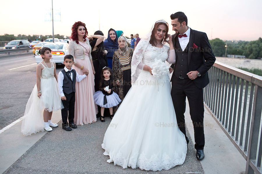 Mcc0070043 . Daily Telegraph<br /> <br /> DT News<br /> <br /> Karon and Karrar pose for photos with family members on Jadriyha bridge , Baghdad before heading off for their wedding party . <br /> <br /> Baghdad 13 May 2016