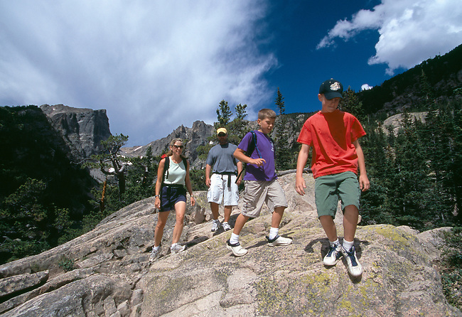 A family of four hike over rocks at Dream Lake in Rocky Mtn Nat'l Park, CO