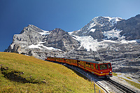 Red rail cars on the Jungfrau railway run below the north face of the Eiger, Mönch and Jungfrau mountains, Bernese Oberland, Switzerland