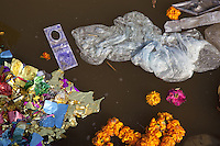 "India. Uttar Pradesh state. Allahabad. Maha Kumbh Mela. Royal bath on Mauni Amavasya Snan (Dark moon). The ritual ""Royal Bath"" is timed to match an auspicious planetary alignment, when believers say spiritual energy flows to earth. Shining Bindi, orange flowers, plastic decorations and plastic waste are floating on the Ganges' river. Indian hindu devotess have offered Shining Bindi to Mother Ganges, considered a deity and also a Lady. A bindi (meaning ""a drop, small particle, dot"") is a forehead decoration worn by married women in India. Traditionally it is a bright dot of red color applied in the center of the forehead close to the eyebrows. The Kumbh Mela, believed to be the largest religious gathering is held every 12 years on the banks of the 'Sangam'- the confluence of the holy rivers Ganga, Yamuna and the mythical Saraswati. The Maha (great) Kumbh Mela, which comes after 12 Purna Kumbh Mela, or 144 years, is always held at Allahabad. Uttar Pradesh (abbreviated U.P.) is a state located in northern India. 10.02.13 © 2013 Didier Ruef"