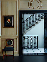 A 16th-century portrait by Antonio Moro hangs above a 19th-century Italian chair in the dining room, which is panelled in oak; the floor is black-stained oak parquet de Versailles, and the staircase beyond is original to the house.