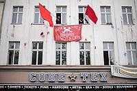 Trotz Corona-Versammlungseinschraenkung gingen am 1. Mai 2020 in Berlin 3.000 Menschen in Berlin-Kreuzberg auf die Strasse. Sie protestierten u.a. fuer die Aufnahme von Gefluechteten aus den ueberfuellten griechischen Fluechtlingslagern und die Unterstuetzung von Automobilkonzernen wegen der Corona-Krise.<br /> Im Bild: Aus einem Haus in der Oranienstrasse werden rote Fahnen geschwenkt.<br /> 1.5.2020, Berlin<br /> Copyright: Christian-Ditsch.de<br /> [NUR FUER REDAKTIONELLE ZWECKE! Werbung nur auf Anfrage beim Fotografen. Inhaltsveraendernde Manipulation des Fotos nur nach ausdruecklicher Genehmigung des Fotografen. Vereinbarungen ueber Abtretung von Persoenlichkeitsrechten/Model Release der abgebildeten Person/Personen liegen nicht vor. NO MODEL RELEASE! Don't publish without copyright Christian-Ditsch.de, Veroeffentlichung nur mit Fotografennennung, sowie gegen Honorar, MwSt. und Beleg. Konto: I N G - D i B a, IBAN DE58500105175400192269, BIC INGDDEFFXXX, Kontakt: post@christian-ditsch.de<br /> Bei der Bearbeitung der Dateiinformationen darf die Urheberkennzeichnung in den EXIF- und  IPTC-Daten nicht entfernt werden, diese sind in digitalen Medien nach §95c UrhG rechtlich geschuetzt. Der Urhebervermerk wird gemaess §13 UrhG verlangt.]