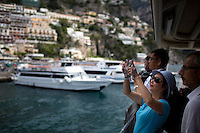 A tourist snaps a picture from an docking ferry on Sunday, Sept. 20, 2015, in Positano, Italy. (Photo by James Brosher)