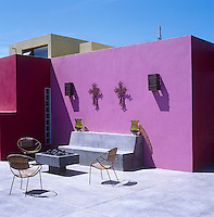 A contemporary take on the traditional Mexican patio; the banquette, floors and barbecue are concrete and antique metal crucifixes hang on the bright pink wall