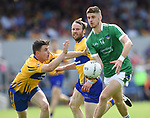 Danny Neville of Limerick in action against Martin Mc Mahon and watched by John Hayes of Clare during their Munster championship quarter-final game in Cusack park. Photograph by John Kelly.