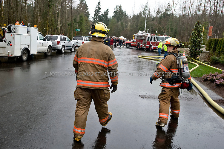 """3/3/2008 -- Woodinville,  Snohomish County, WA, USA.Smoke billows behind a fireman at the scene where three multi-million-dollar homes were destroyed by arson in an apparent act of domestic terrorism and that also damaged two others in the Maltby area of Snohomish County, east of Seattle, Wash. Near the burned homes, a spray-painted sign with the initials of the Earth Liberation Front was found. Local TV news showed the sign that read: """"Built Green? Nope black! McMansions in RCDs r not green. ELF"""".The homes were all unoccupied and were part of Seattle 'Street of Dreams' homes in the Quinn's Crossing development near Highway 522. The homes that burned were between 4,200 and 4,750 square feet in size, with prices up to nearly $2 million. The homes were built to be environmentally friendly an dused high-efficiency insulation and recycled materials...©2008 Stuart Isett. All rights reserved."""