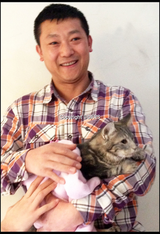 BNPS.co.uk (01202 558833)<br /> Pic: DFRS/BNPS<br /> <br /> Teddy the cat with owner Mr Fu.<br /> <br /> A cat that got stuck behind a wall for 24 hours had to be rescued by firefighters with a special camera used to find people trapped in collapsed buildings.<br /> <br /> The Dorset and Wiltshire crew used a snake-eye camera to locate the mischievous moggy so they could cut a hole in the wall and get it out.<br /> <br /> The pet was covered in dust and very thirsty after its ordeal but still had his nine lives intact.<br /> <br /> It got into the wall cavity through a water mains access under the stairs of a ground floor block of flats in Dorchester, Dorset, and climbed about 6ft up the void behind the wall before getting stuck.