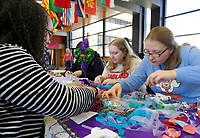 NWA Democrat-Gazette/DAVID GOTTSCHALK Brittany Miller (from left), a senior at the University of Arkansas, Sarah Luther, a junior, and Olga Brazhkina, a junior, search for items to decorate their masks Monday, February 12, 2018, during the Beads and Bling It's a Mardi Gras Thing in the Arkansas Union International Connections Lounge on the campus in Fayetteville. The celebration, hosted by University Programs, offered King Cake, mask decorating, trivia and other activities.