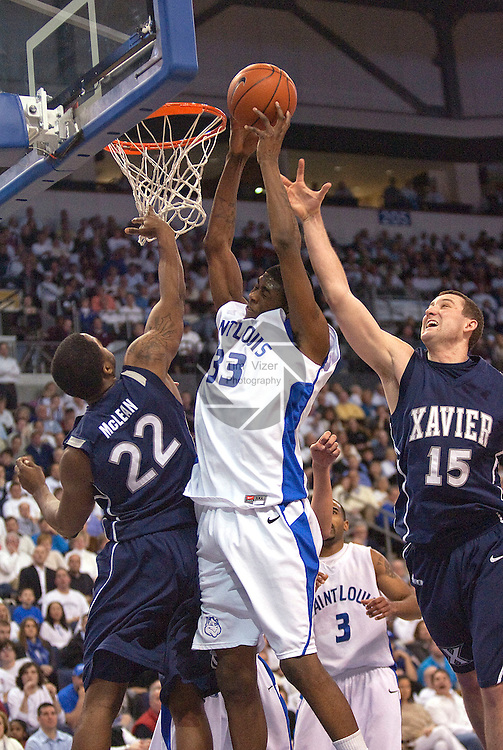 February 24,  2010                 Xavier forward Jamel McLean (22) and Xavier forward Andrew Taylor (15) try to get the loose ball during a rebound in the second half.  In center is Saint Louis forward Willie Reed (33).  The St. Louis University Billikens hosted the Xavier University Musketeers on Wednesday February 24, 2010 at the Chaifetz Arena, located on the campus of St. Louis University near downtown St. Louis.  Xavier ended Saint Louis' six-game winning streak, with a final score of 73-71.