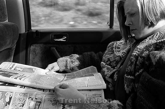 Laura Nelson in the car, reading newspaper<br />