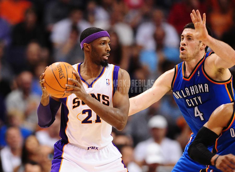 Mar. 30, 2011; Phoenix, AZ, USA; Phoenix Suns forward (21) Hakim Warrick controls the ball under pressure from Oklahoma City Thunder forward (4) Nick Collison at the US Airways Center. Mandatory Credit: Mark J. Rebilas-.