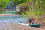 People float down the Buffalo River in Arkansas in canoes. Rocks can be seen jutting out into the river as they go around the bend.