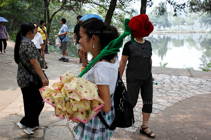 A tour guide holds a rose shaped loud speaker at Mao Zedong's birthplace in Shaoshan, Hunan Province, China on 12 August 2009.