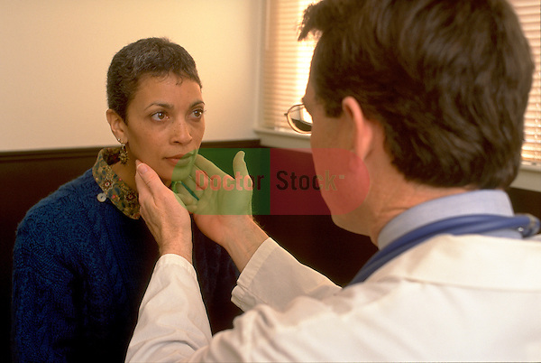doctor examining glands in throat of woman